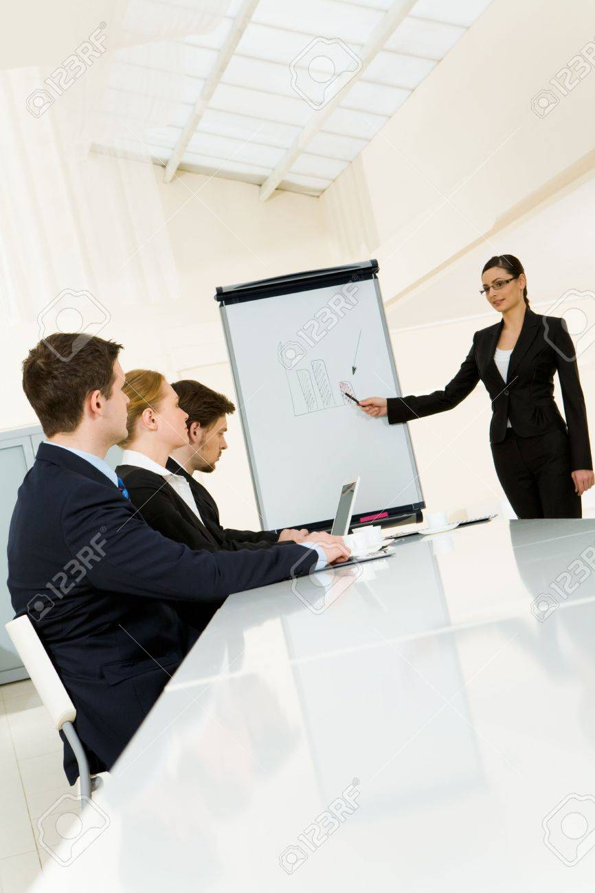 Smart and confident employee pointing at whiteboard while presenting her ideas to business partners Stock Photo - 4681026