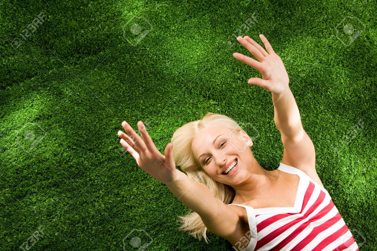 Above view of young glad female lying on green grassland and stretching her arms Stock Photo - 4941346