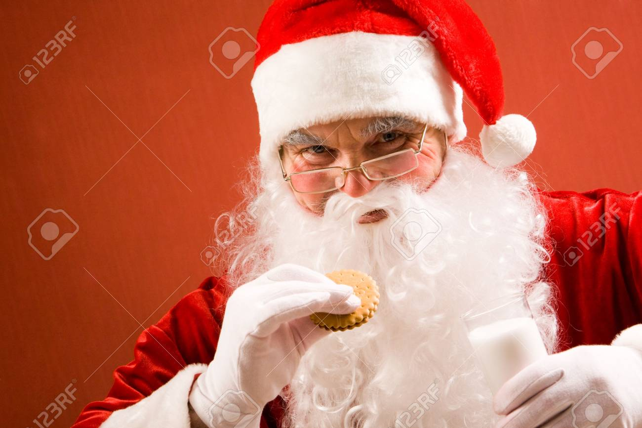 Photo of happy Santa Claus in eyeglasses looking at camera while drinking milk with bisquit Stock Photo - 6106965