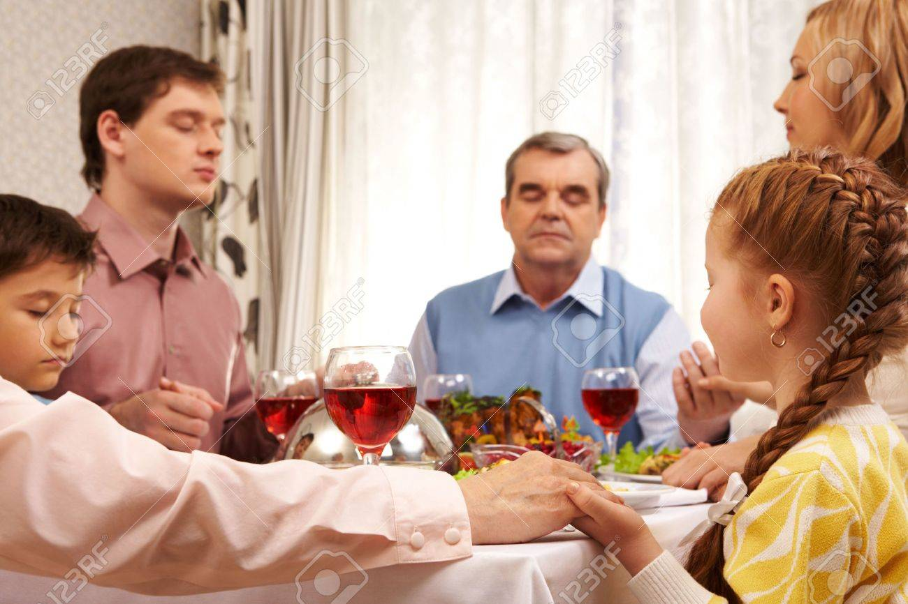 Image of family members praying at festive table while holding each other by hands Stock Photo - 6107401