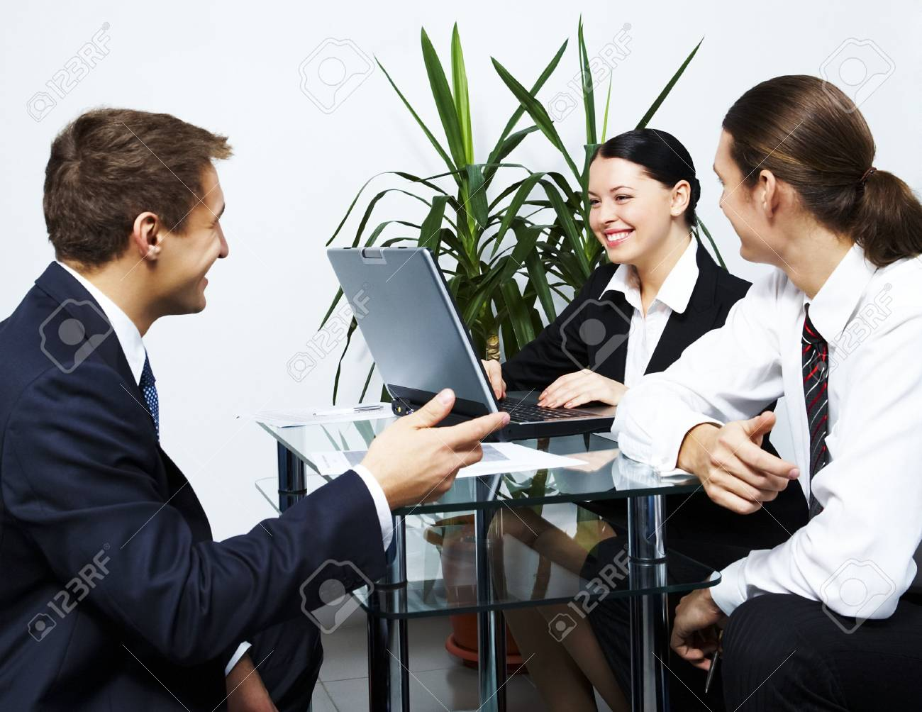 Photo of co-workers looking at each other with smiles while working Stock Photo - 6226571