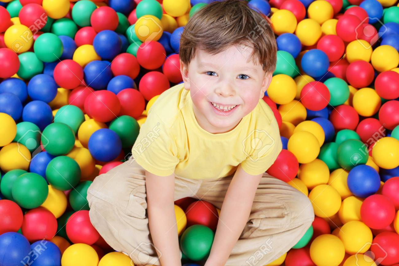 Happy lad seated on colorful balls and looking at camera with smile Stock Photo - 6670122