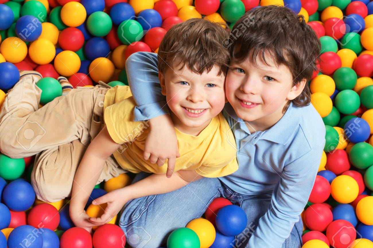Happy lad embracing his brother and both looking at camera with smiles Stock Photo - 6670129
