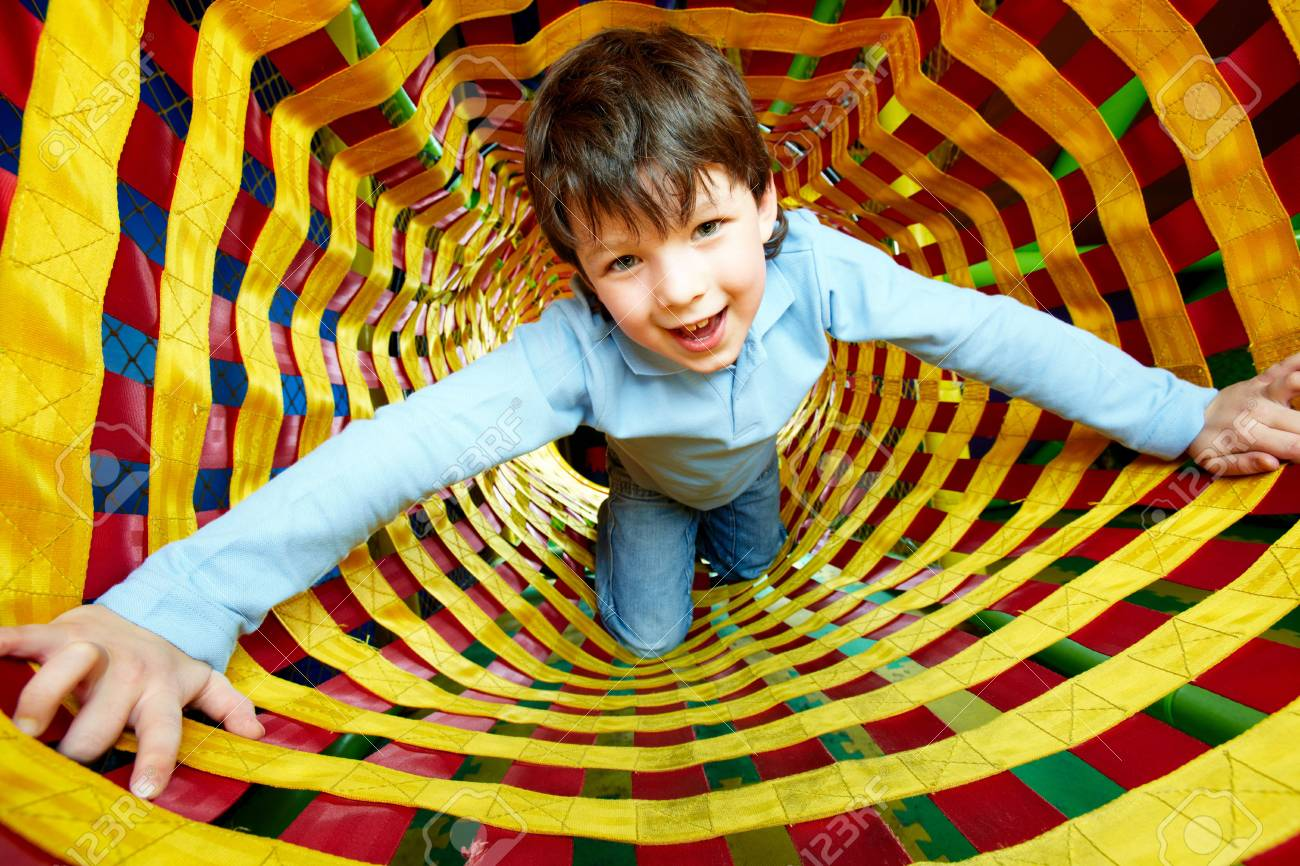 Happy lad looking at camera while having fun inside toy tunnel Stock Photo - 6670124