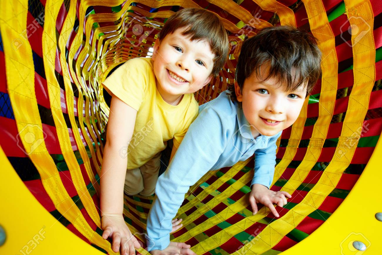 Happy siblings looking at camera while having fun inside toy tunnel Stock Photo - 6670154