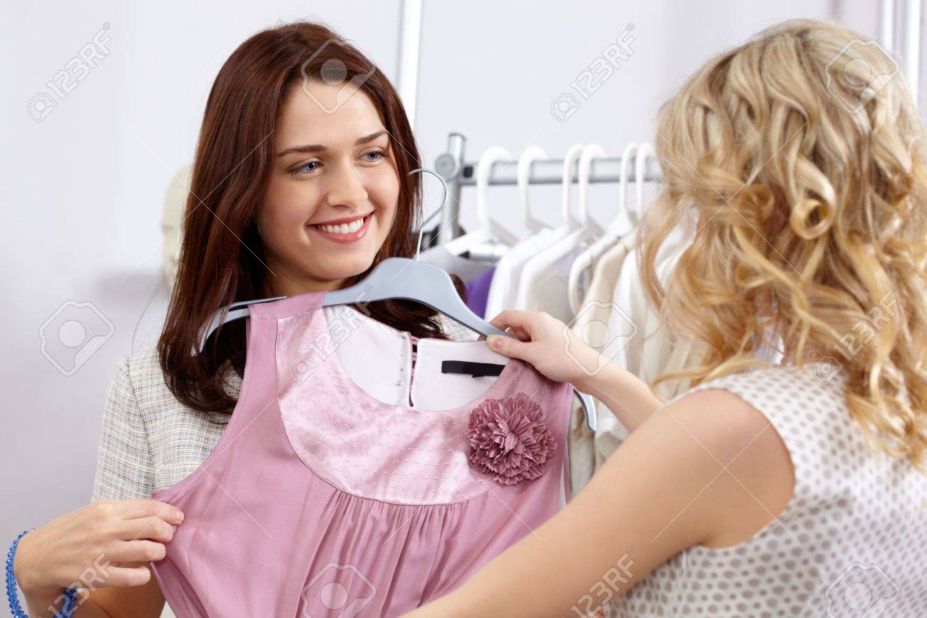 Image of pretty girl trying on tanktop with helpful assistant near by in the department store Stock Photo - 6700358