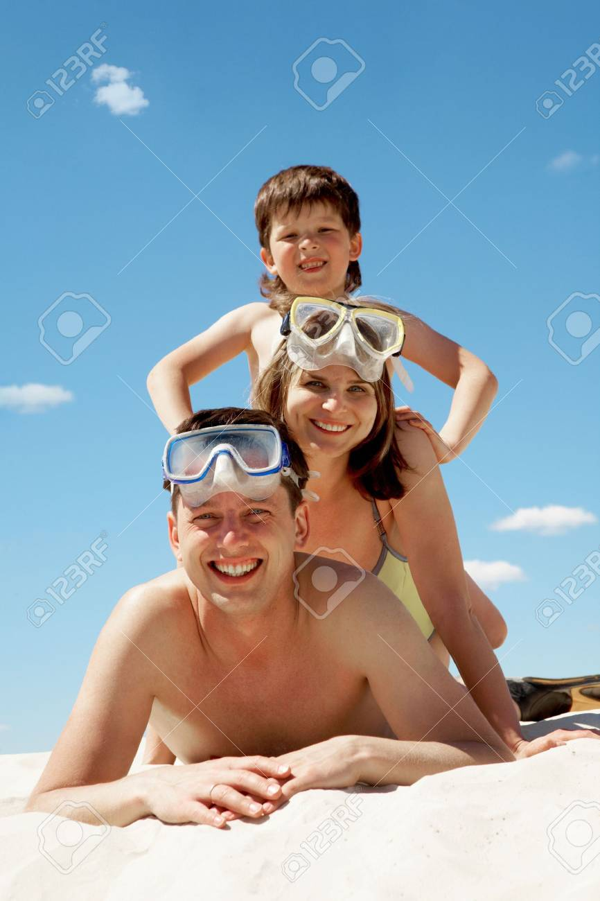 Portrait of cheerful couple in goggles and their son lying on sand Stock Photo - 6714220