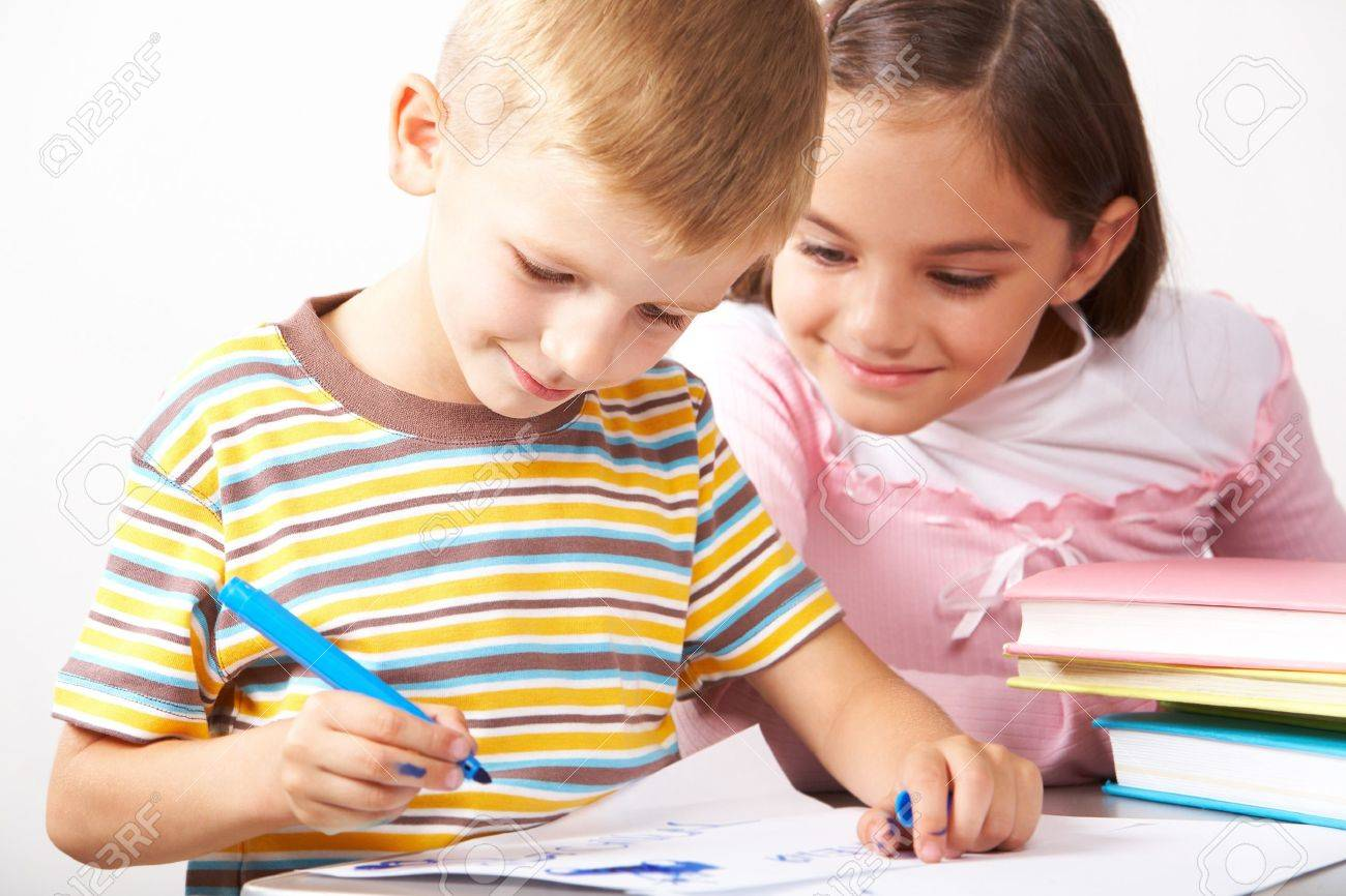 Portrait of boy drawing on the paper with curious girl looking at it near by Stock Photo - 7409189