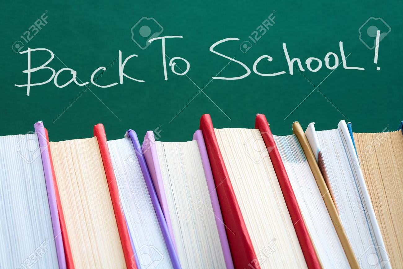 Colorful stack of textbooks on background of blackboard Stock Photo - 7409180