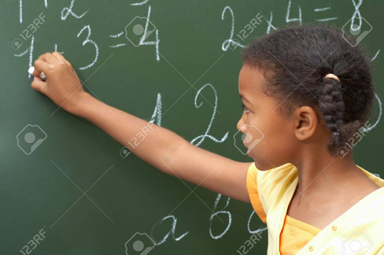 Portrait of smart schoolchild standing at blackboard and doing sums Stock Photo - 7484410