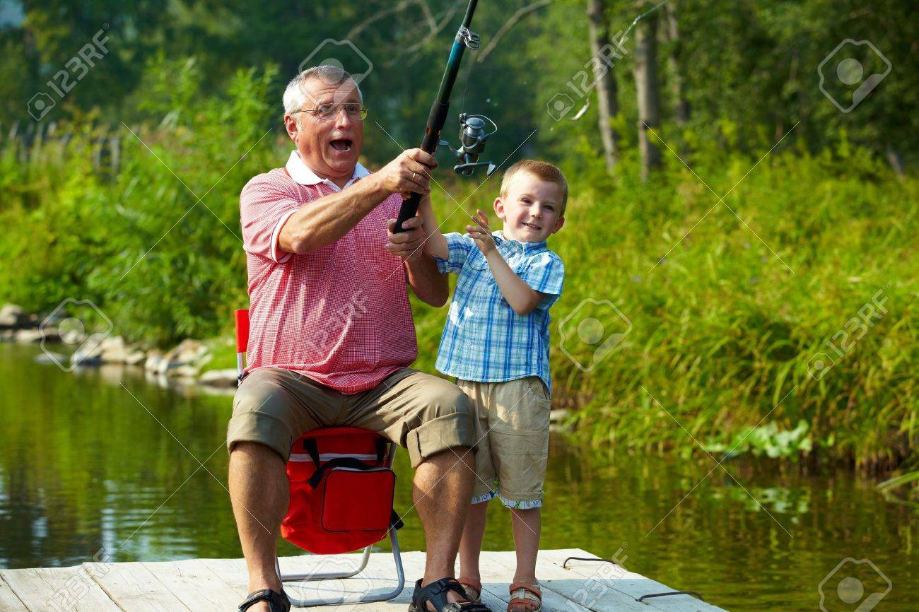 Photo of grandfather and grandson throwing fishing tackle in natural environment Stock Photo - 7601941