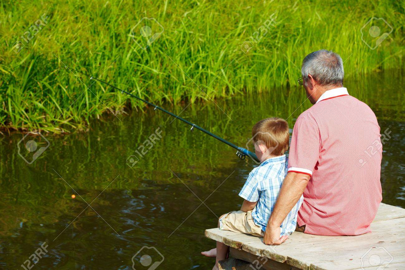 Photo of grandfather and grandson sitting on pontoon and fishing on weekend Stock Photo - 7601958