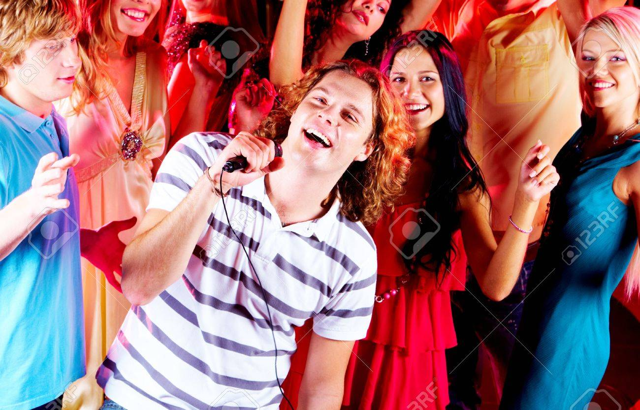 Photo of happy guy singing in mic at party with company of friends dancing behind Stock Photo - 7695327