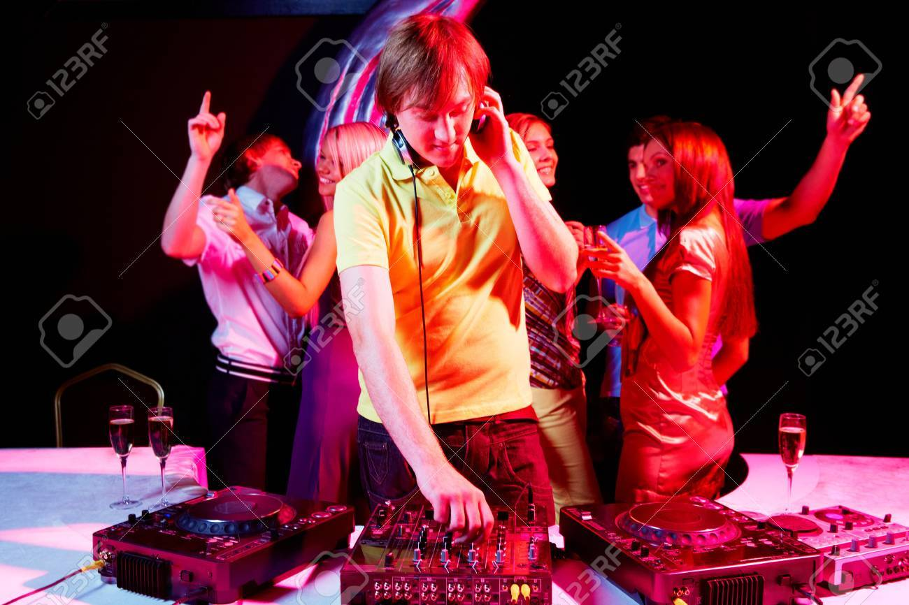 Portrait of handsome deejay working with dancing teens on background Stock Photo - 7695314