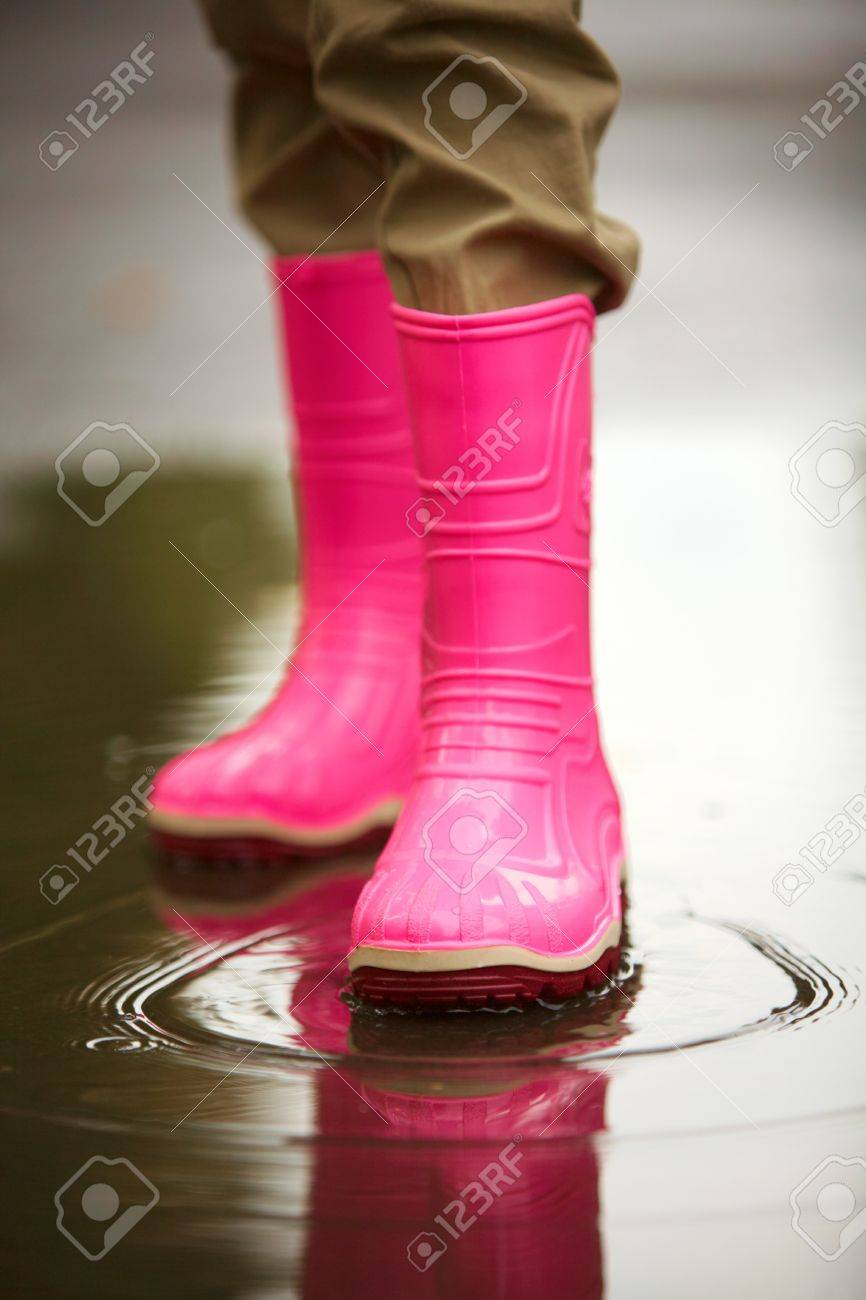 Legs of child in rainboots standing in puddle Stock Photo - 7695481
