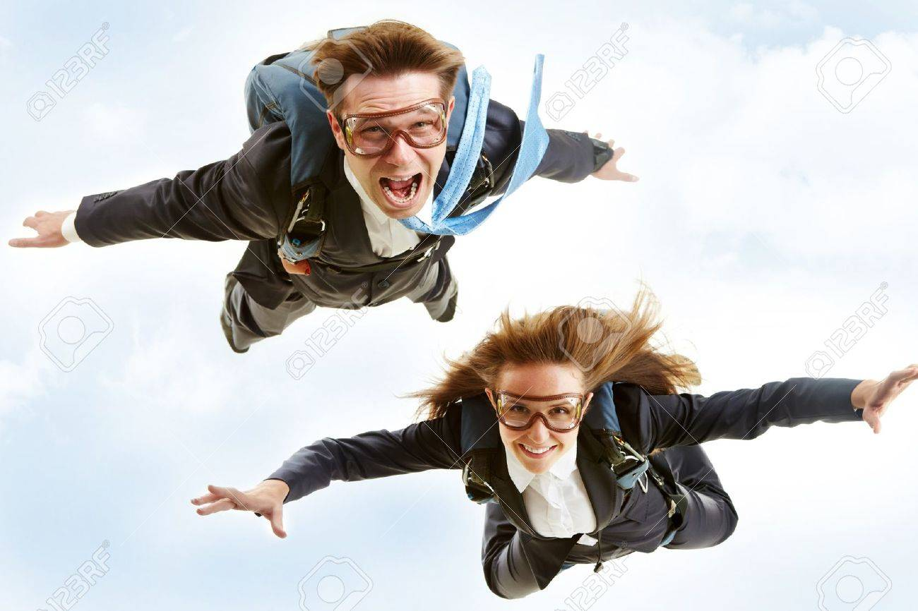Conceptual image of young business partners flying with parachutes on their backs Stock Photo - 7873855