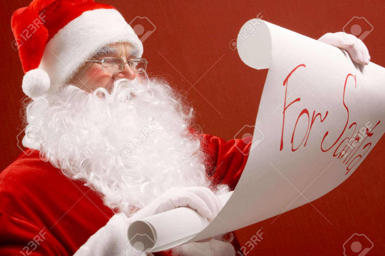 Portrait of cute Santa Claus reading big letter on red background Stock Photo - 7965231