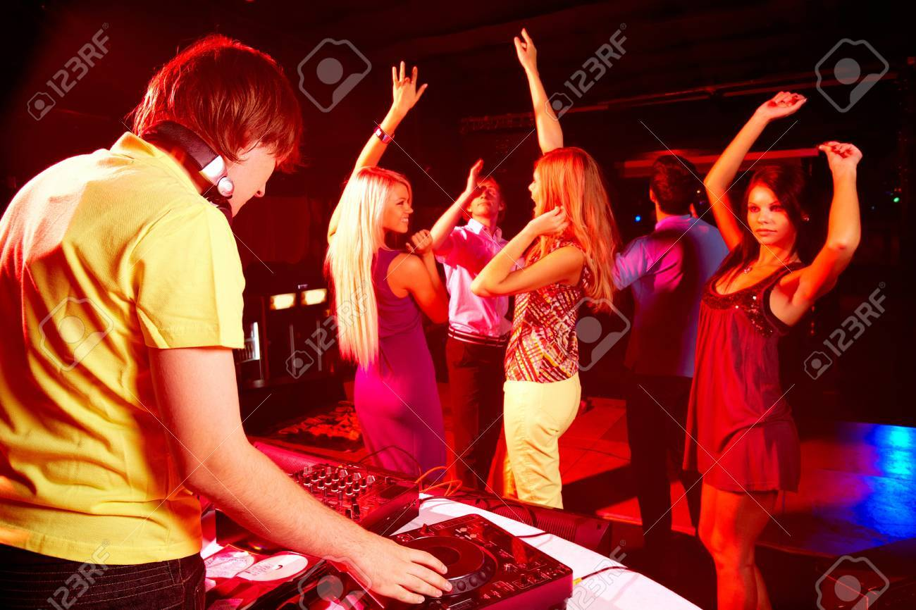 Smart deejay spinning turntables with dancing teens on background Stock Photo - 8227429
