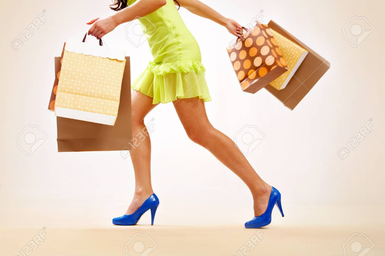 Legs of lady with colorful paper bags in move Stock Photo - 8229318