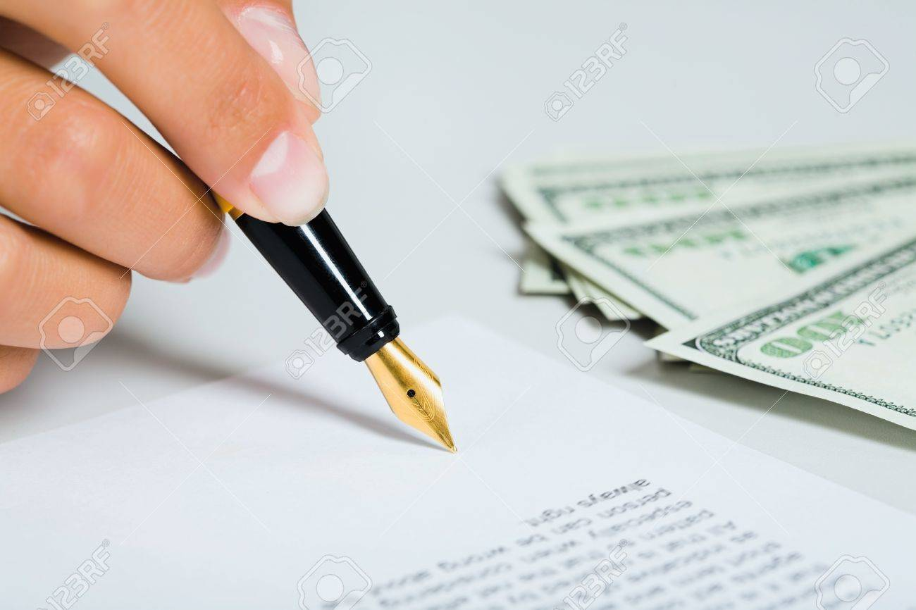 Female hand is signing the business document near money Stock Photo - 8313128