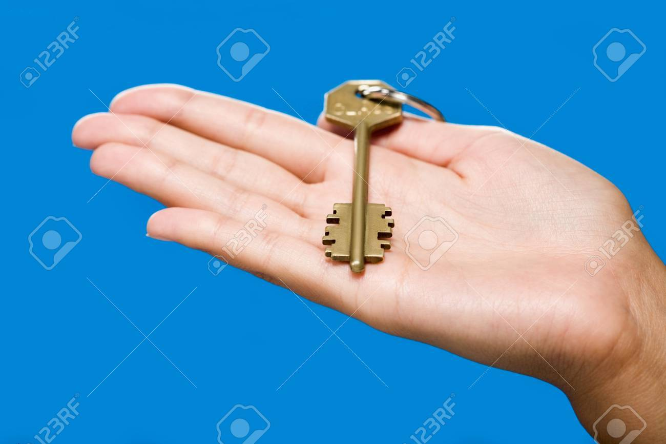 Golden key lying on the hand on the blue background Stock Photo - 8313120