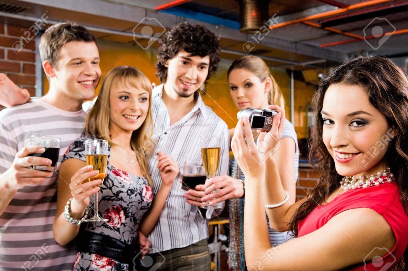 Image of beautiful smiling woman holding the camera at the evening-party Stock Photo - 8314281