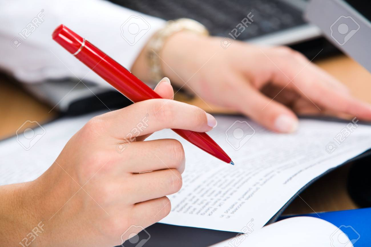 Close-up of female hand holding the red pen Stock Photo - 8314198