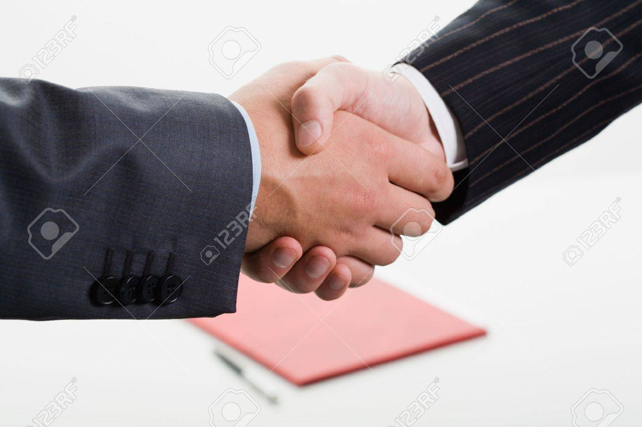 Close-up of shaking hands making an agreement on the background of folder and pen Stock Photo - 8356623