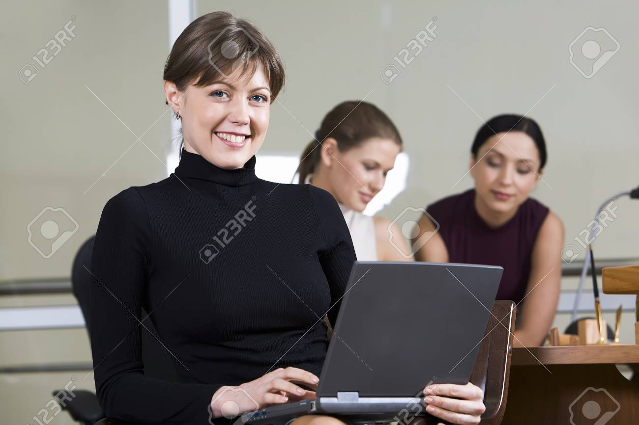Portrait of smiling woman with the laptop on her knees sitting in the cafe and two girls on the background Stock Photo - 8357341