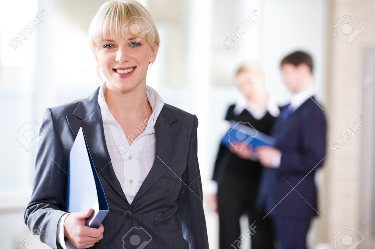 Portrait of young pretty professional holding a folder on the background of people Stock Photo - 8357360