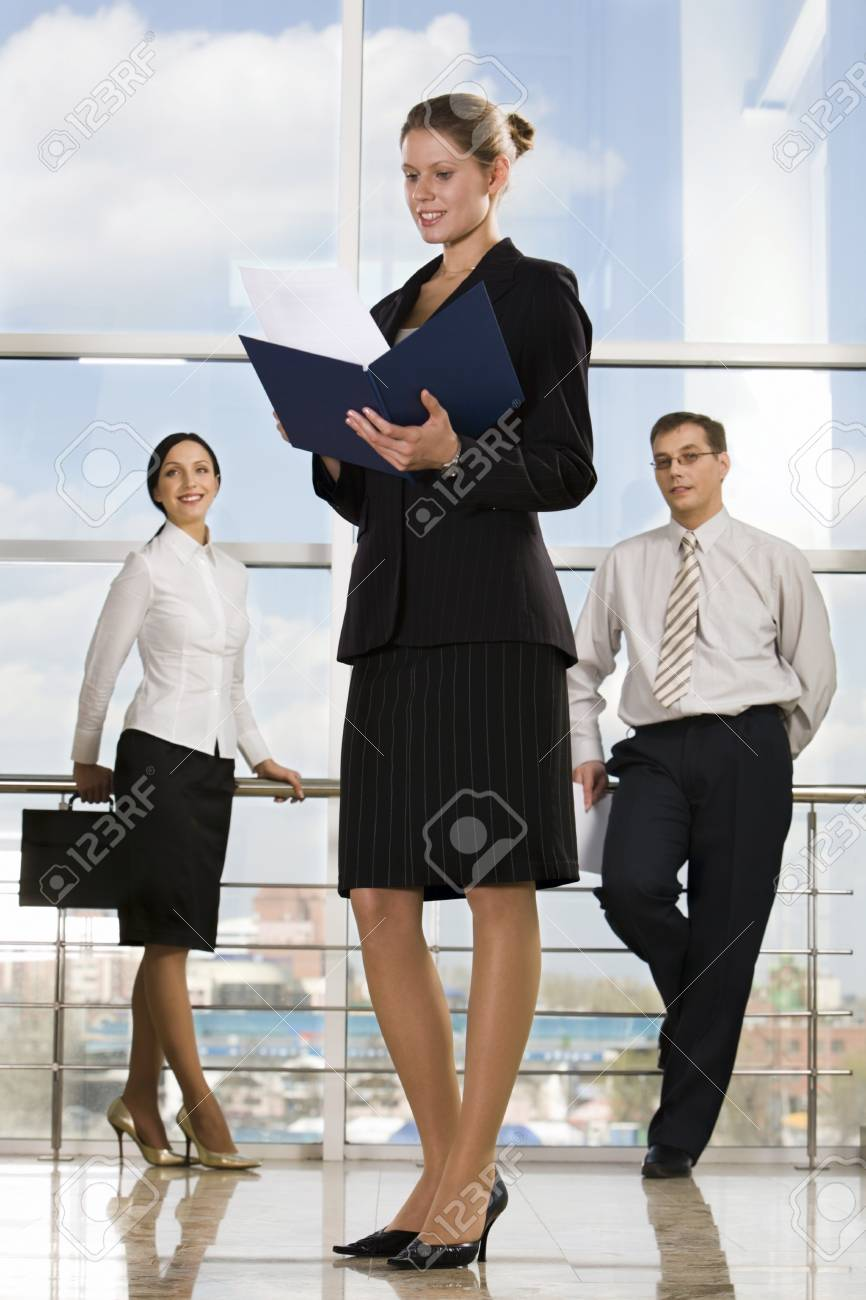 Smiling Caucasian businesswoman reading documents in modern office building and two businesspeople on the background Stock Photo - 8357364