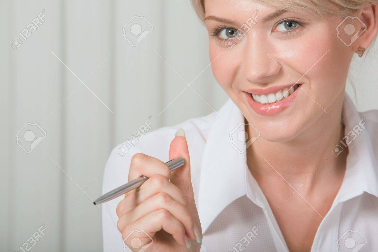 Young beautiful smiling white collar worker is holding the pen Stock Photo - 8357349