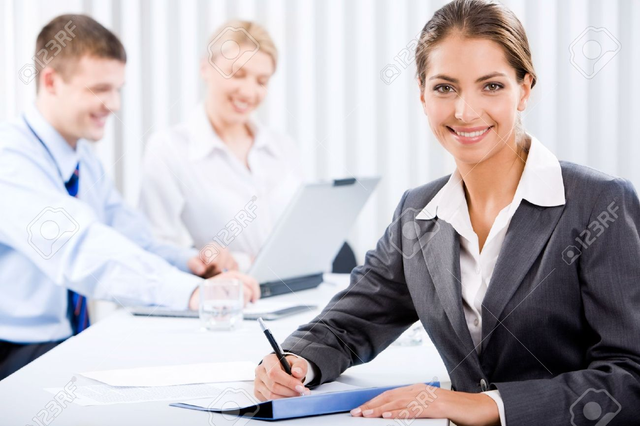 Portrait of happy business woman sitting at the table on the background of her coworkers Stock Photo - 8393840
