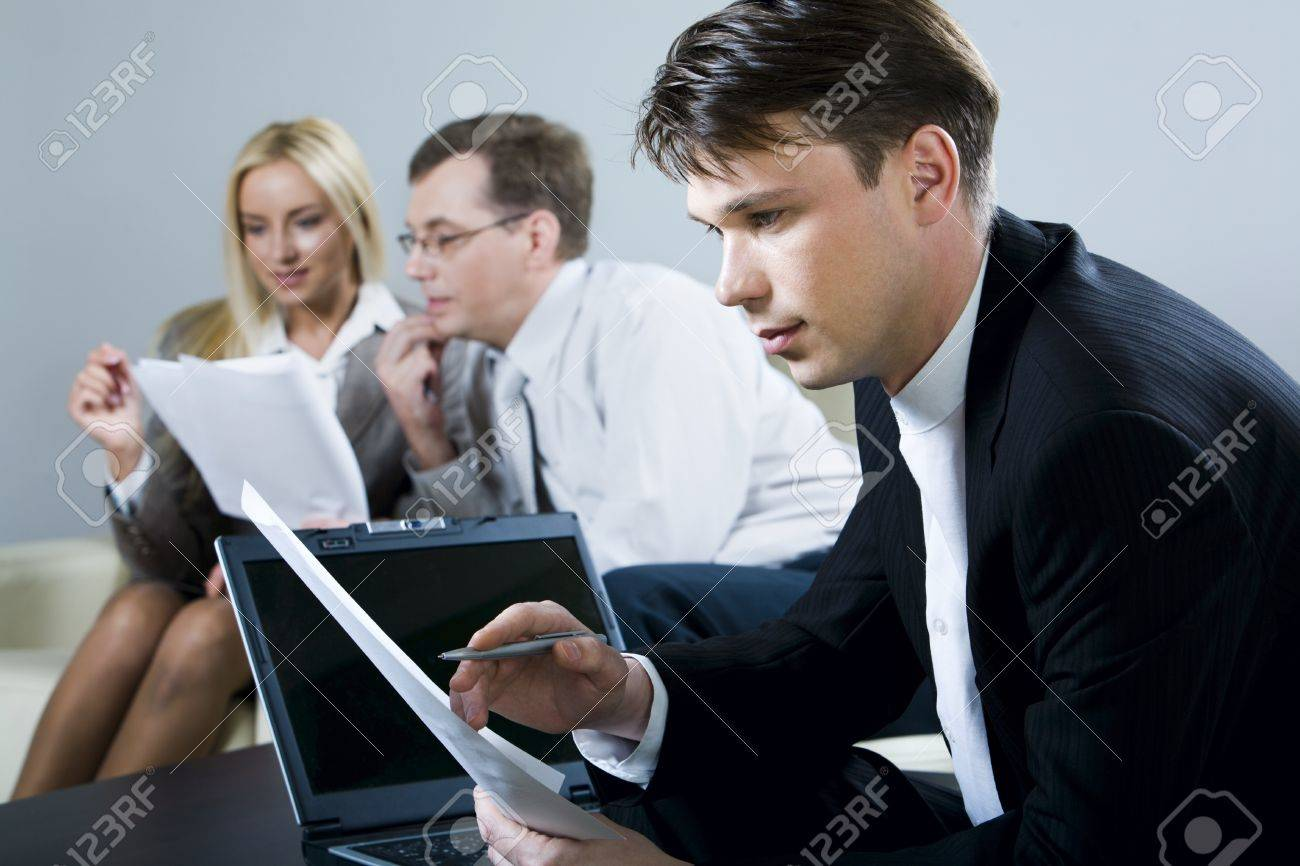 Portrait of serious man reading a document with open laptop and two reading businesspeople on the background Stock Photo - 8394462