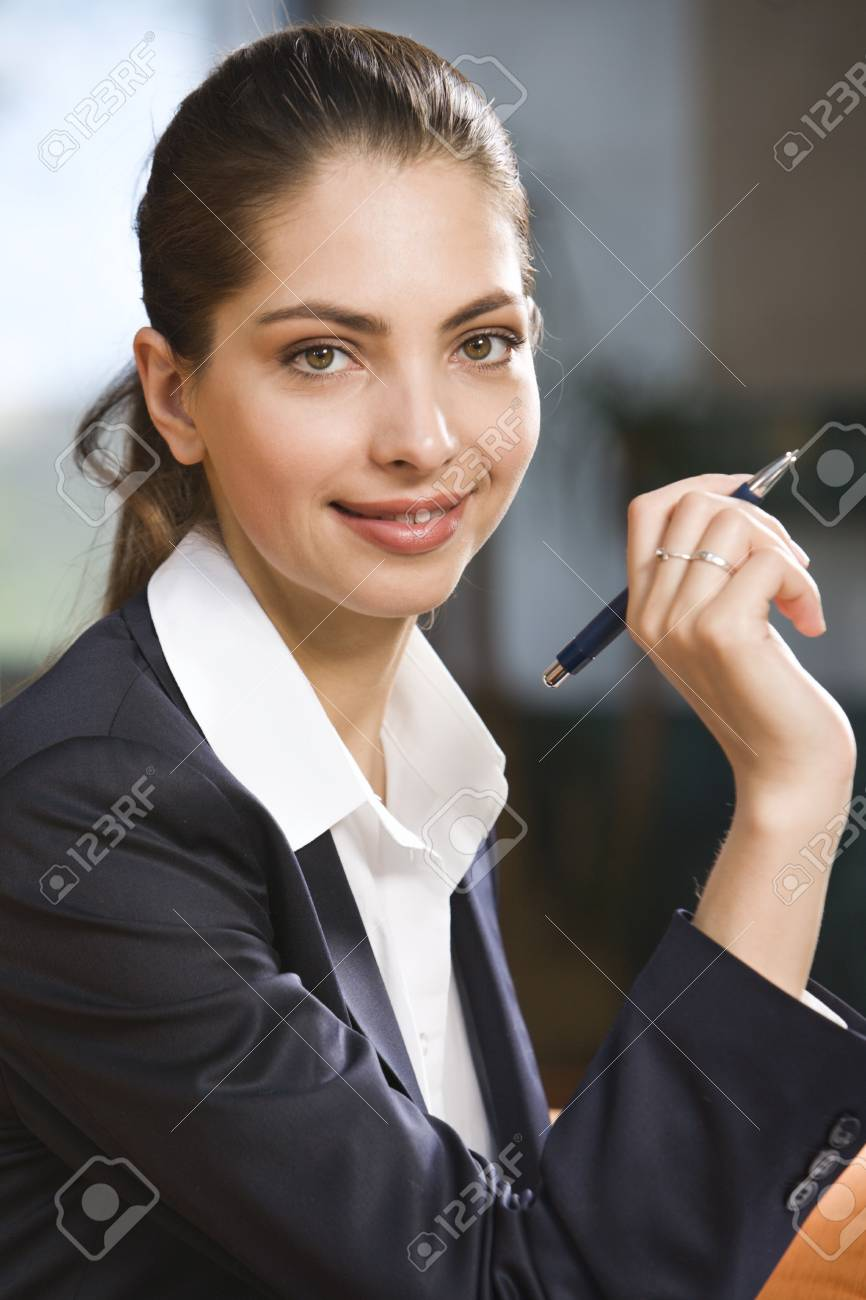 Pretty brunette with pen looking at camera Stock Photo - 8394568