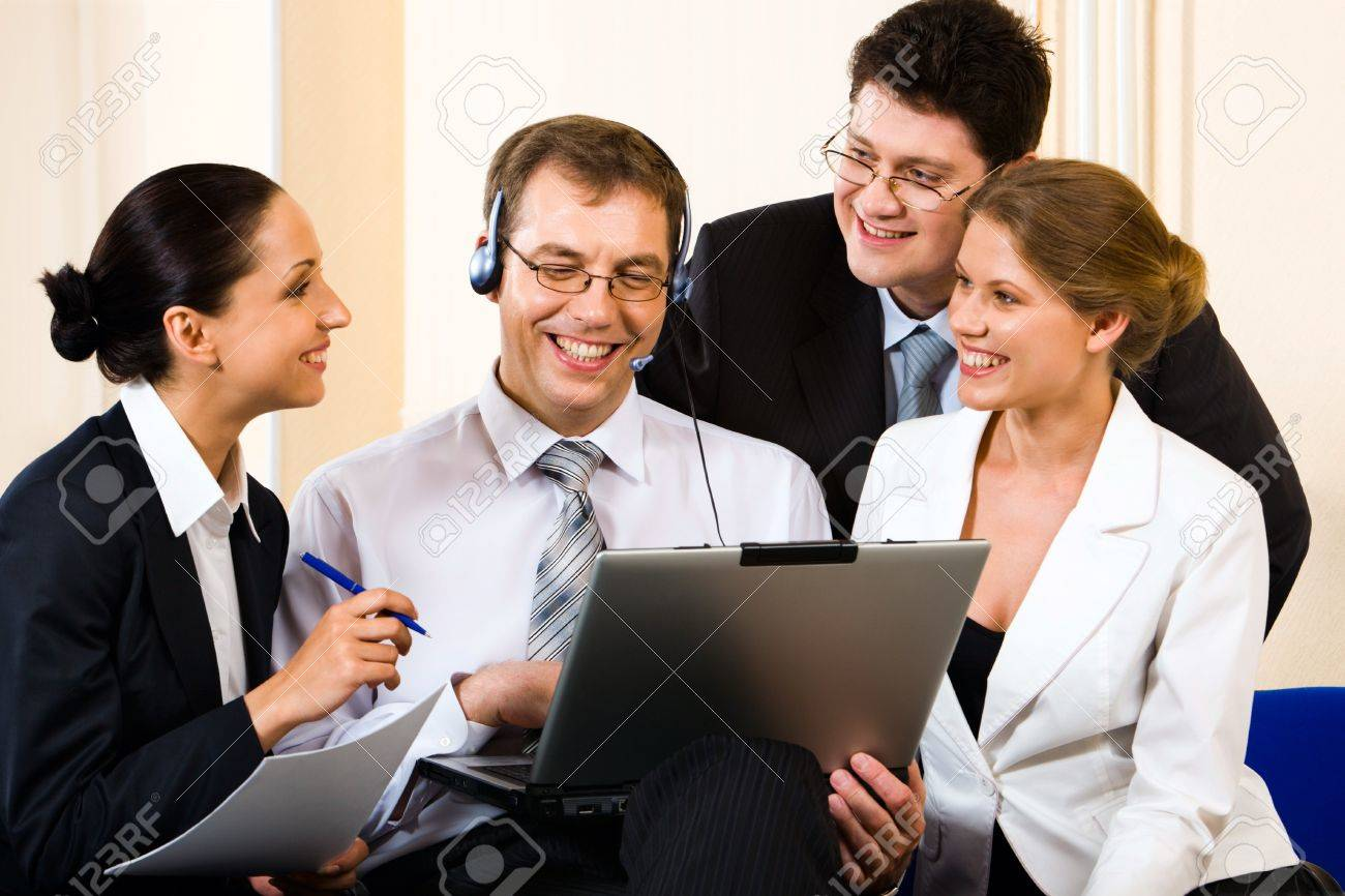Team of four young business people gathered together around the laptop communicating with another department Stock Photo - 8394828