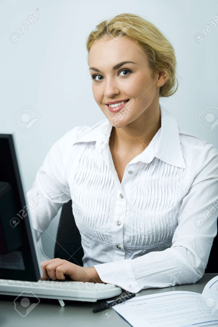 Beautiful smiling blond businesswoman typing on her computer Stock Photo - 8398873