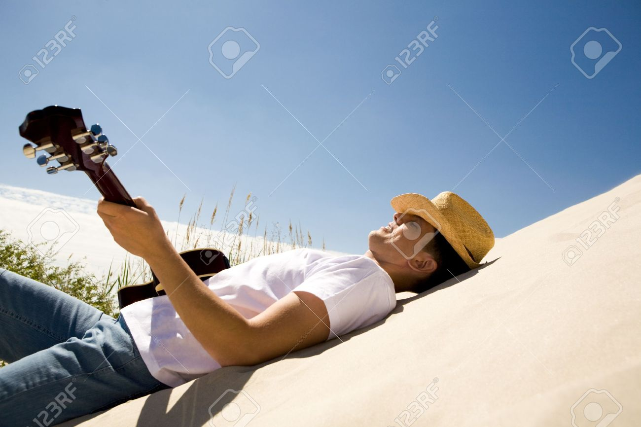 Image of happy man in cowboy hat playing the guitar while relaxing on sandy beach Stock Photo - 8435095