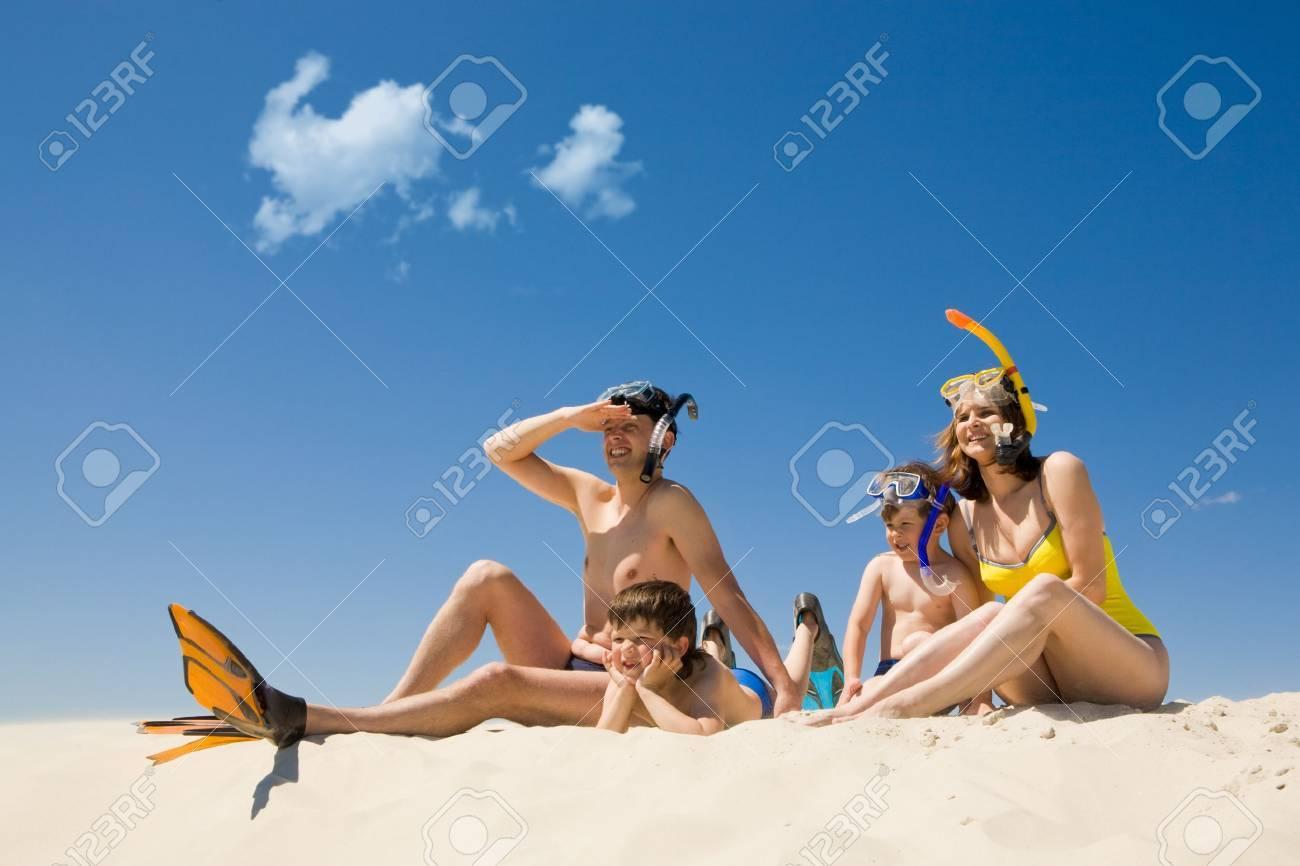 Portrait of modern family sitting on sandy beach against blue sky Stock Photo - 8435093
