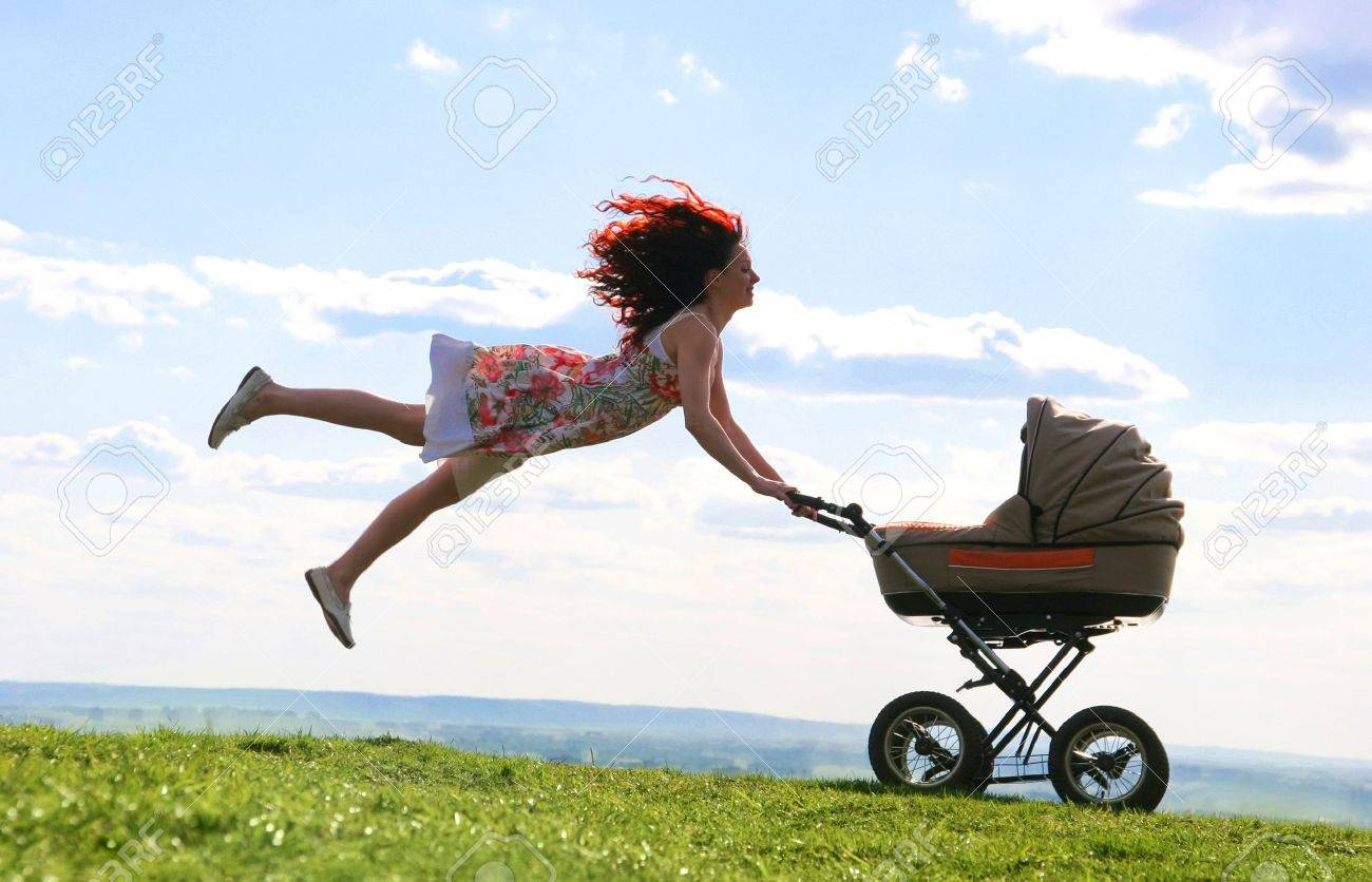 Joyful female jumping over green grassland while holding carriage with baby Stock Photo - 8434364