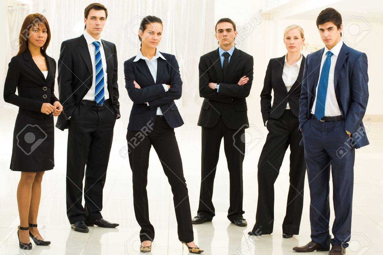 Portrait of confident well-dressed business people standing in semicircle with smart lady in center Stock Photo - 8447364