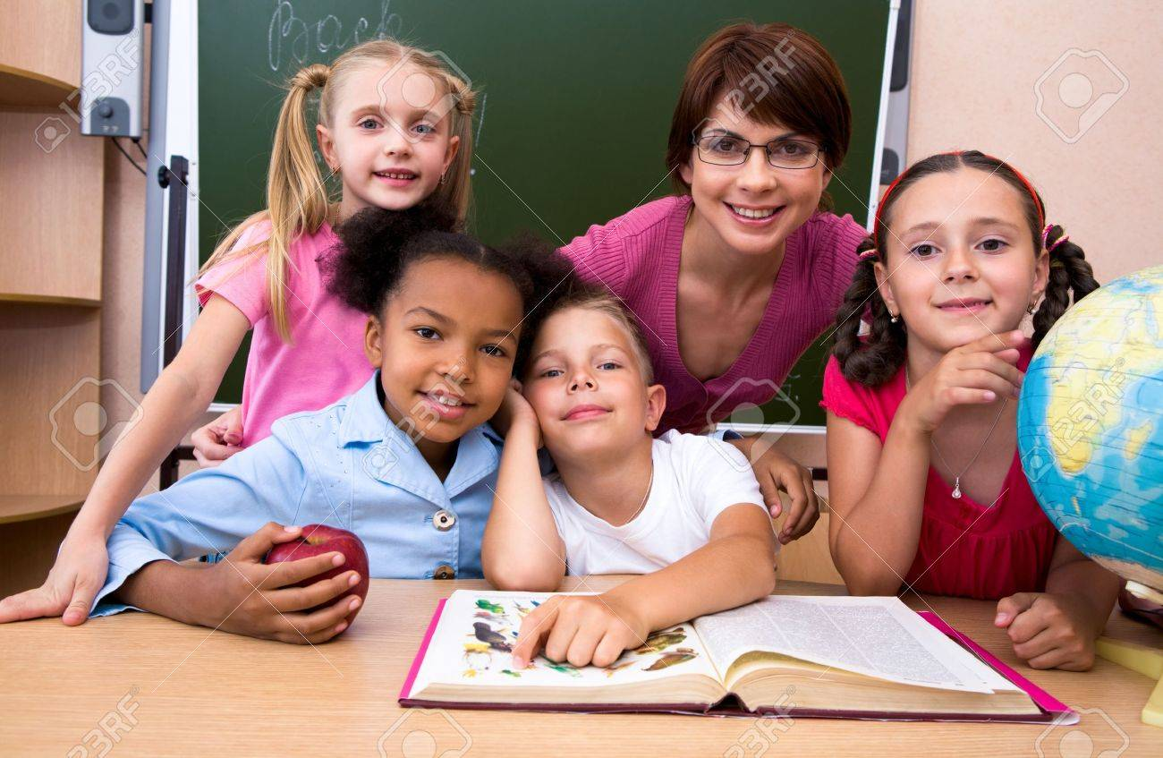 Portrait of teacher and children looking at camera in the classroom Stock Photo - 8455379