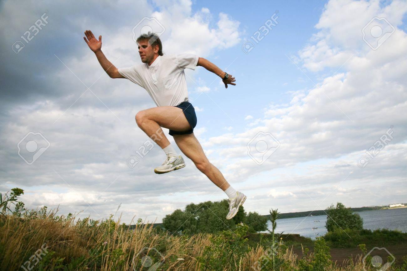 Horizontal image of active man jumping near lake Stock Photo - 8455377