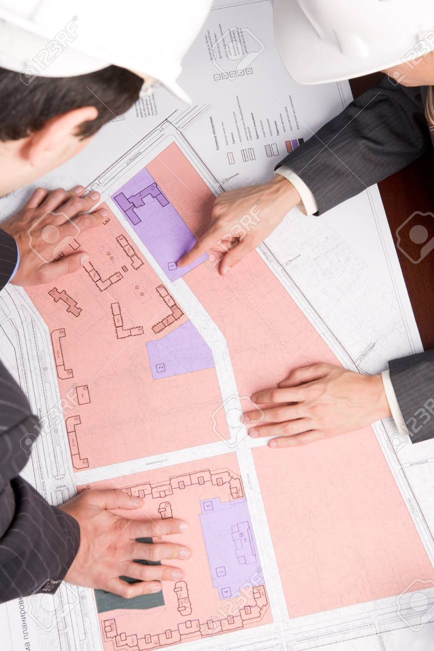 Close-up of engineers looking at blueprints with sketches of projects Stock Photo - 8475867