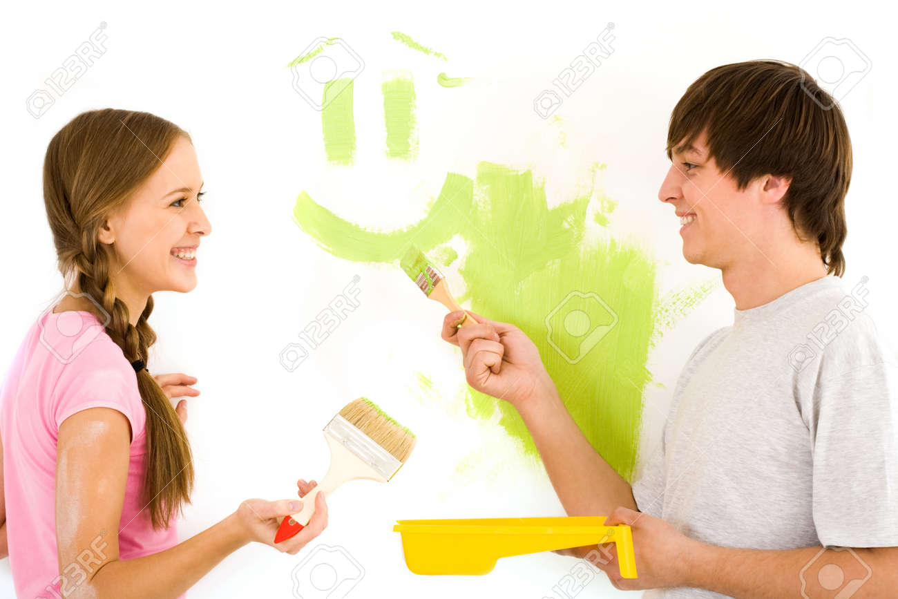 Young happy couple painting walls in new house Stock Photo - 8479169