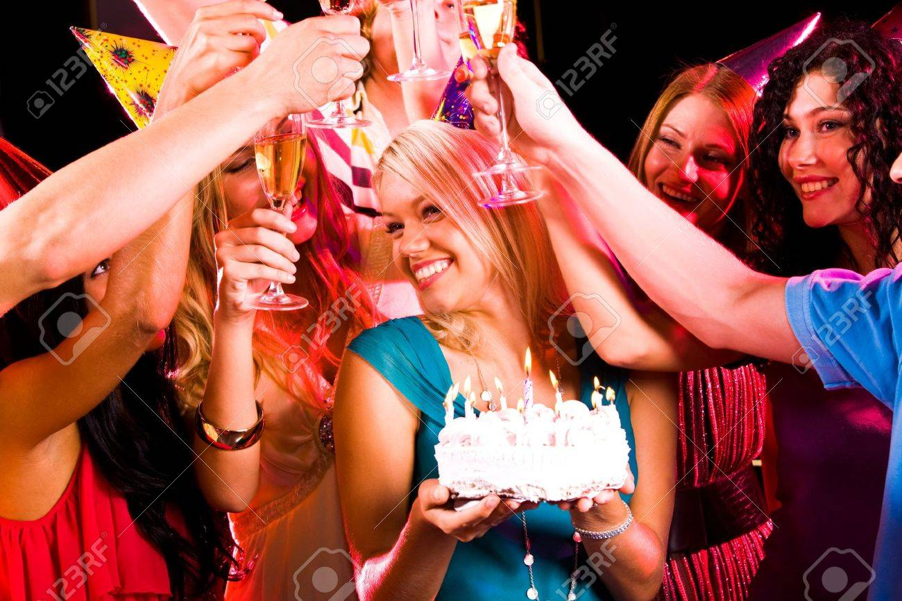 Portrait of joyful girl holding birthday cake surrounded by her friends with flutes Stock Photo - 8507037
