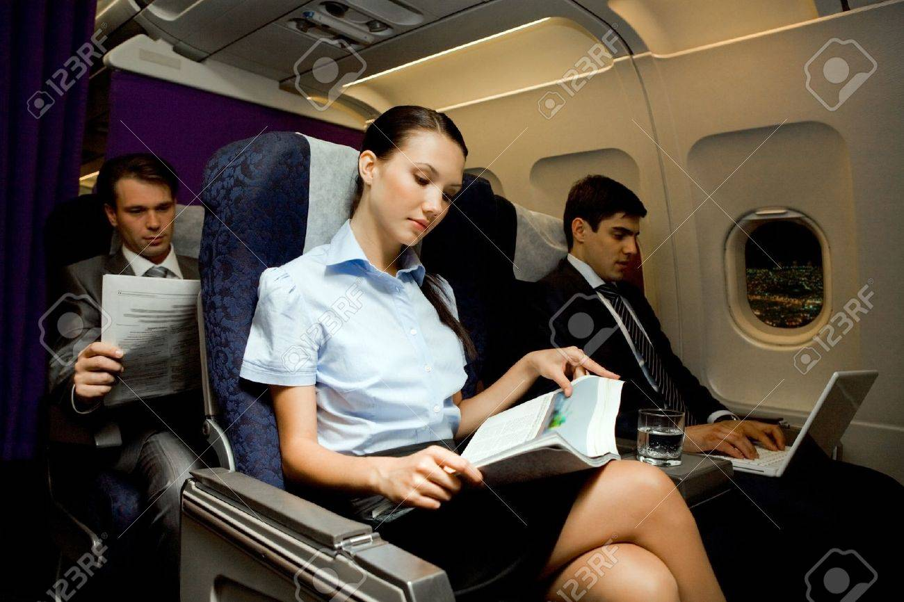 Image of pretty girl reading magazine while handsome man typing next to her in airplane Stock Photo - 8507981