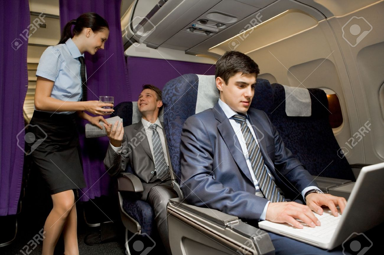 Image of busy male typing on laptop with pretty stewardess giving glass of water to successful businessman on background Stock Photo - 8507980