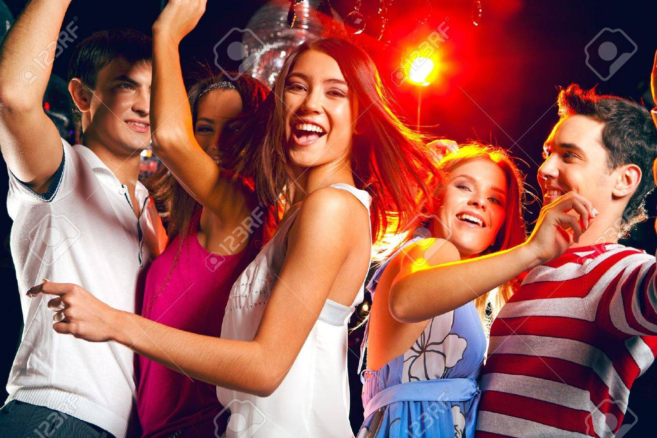 Pretty clubber dancing surrounded by her friends and looking at camera with smile Stock Photo - 8508188
