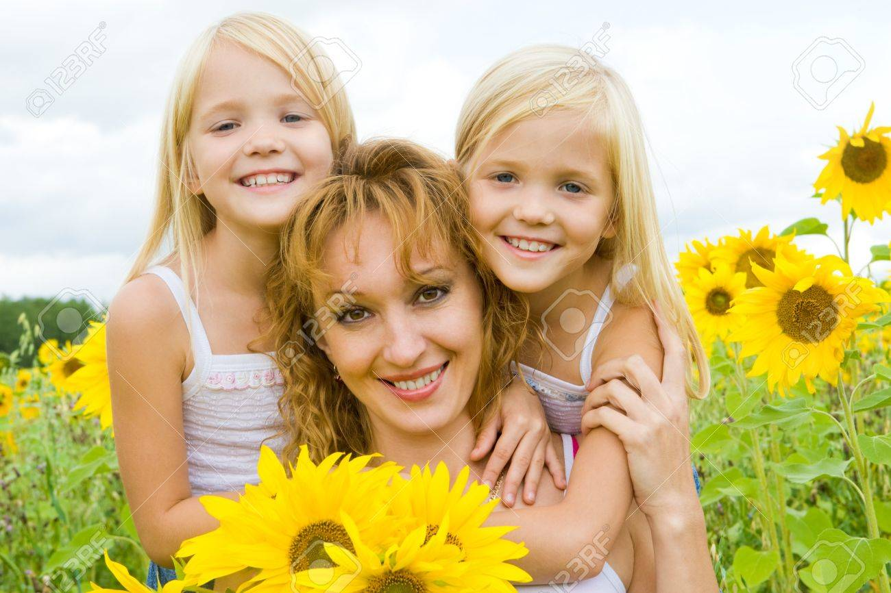Portrait of cute twins embracing their mother with smiles in sunflower field Stock Photo - 8508059